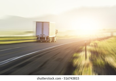 beautiful scenic view of truck on the asphalt road with sunrise/sunset.