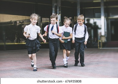 Beautiful school children active and happy on the background of school in uniform