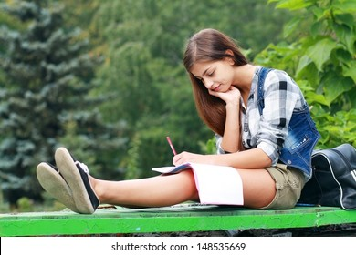 Beautiful school or college girl sitting on the bench with book and bag studing in a park