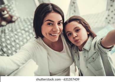 Beautiful school girl and her mom are hugging, looking at camera and smiling while playing in girl's room at home