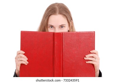 Beautiful school girl peeping from behind her red book isolated on white