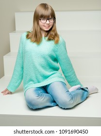 Beautiful schoolgirl girl in glasses sits on a white staircase. The concept of happy people, childhood.
