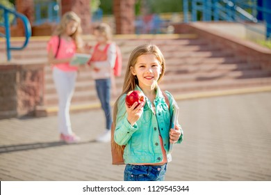 beautiful schoolgirl holding an apple against the background of the school