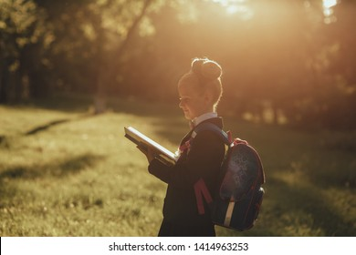 beautiful schoolgirl reads a book in the park, in school uniform, with a school bag, profile view, outdoor, at sunset
