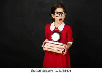A beautiful schoolgirl in a red dress with a books and clock on a black background