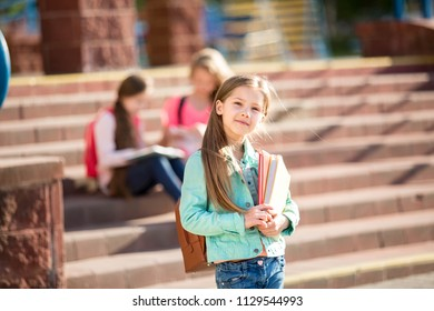beautiful schoolgirl standing with book in front of school background