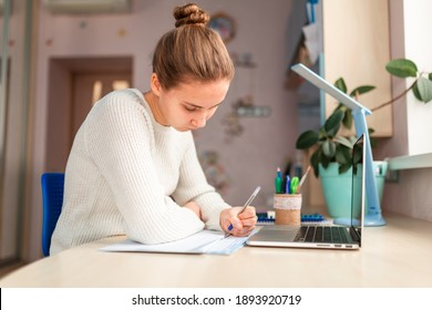 Beautiful schoolgirl studying at home doing school homework. Training books and notebook on the table. Distance learning online education