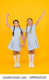 Beautiful schoolgirls. Back to school concept. Hairdresser salon. Cute schoolgirls. Girls with braided hair style. Cheerful schoolgirls yellow background. Little girls playing with cute braids.