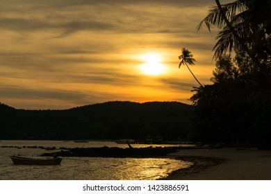 beautiful sea beach landscape at sunset time. silhouetted coconuts tree and mountain with sunset sky
