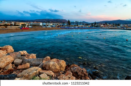 Beautiful sea with evening soft light of the sunset against cloudy sky with sun in Gouves on Crete. Greece