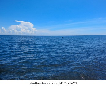 Beautiful sea Landscape with blue sky and tiny clouds on sunny day in Indonesia. Seascape with sea horizon and almost clear deep blue sky. Calm Sea and Blue Sky Background. Blue sea water surface on s