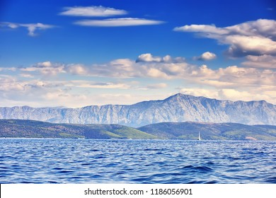 The Beautiful sea landscape, sailboat sailing on the distance on great majestic mountains background, romantic cruise in the Adriatic sea, Croatia