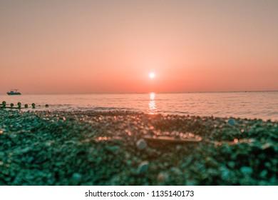 Beautiful sea landscape in Turkey. Sunrise on beach in the morning. Sun rises over the sea. Pink colors, sea shore