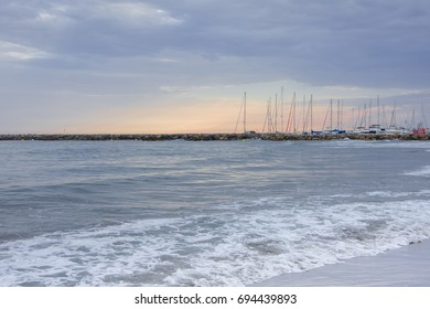 Beautiful sea landscape with waves in mild pink sunset romantic light with sailing boats on the background