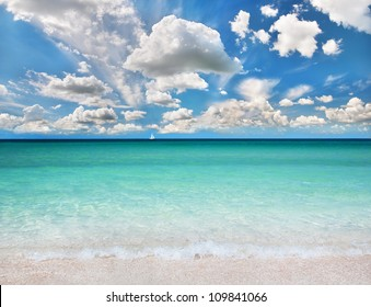 Beautiful sea summer or spring abstract background. Golden sand beach with blue transparent ocean, white sailer and blue sky.