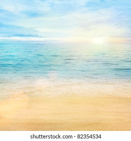 Beautiful sea summer or spring abstract background. Golden sand beach with blue ocean and cloudscape and sunset in the back.
