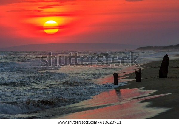 Beautiful sea sunset with breaking waves onto a sandy sea shore. Scenic landscape of Black Sea coast