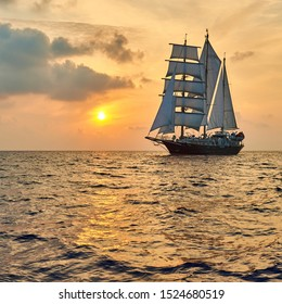 Beautiful sea at sunset and a sailing ship under white sails. Yachting