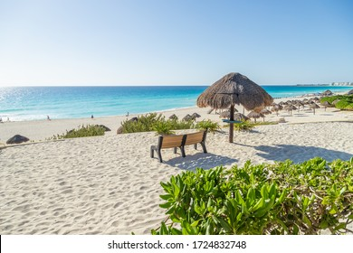 Beautiful sea view during dawn. Bench and straw umbrella on the beach overlooking the Caribbean Sea