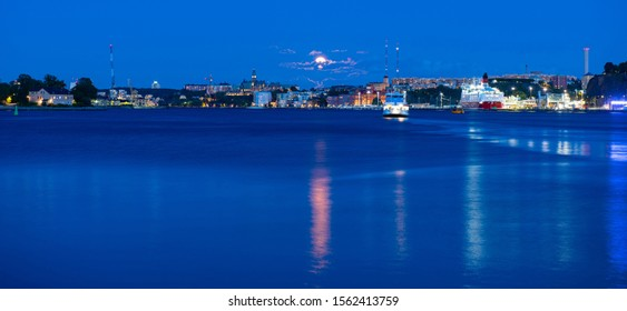 Beautiful sea view on Stockholm in dusk and ferry floating at Baltic Sea, Sweden. Moonlight sky.