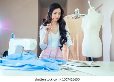 A beautiful seamstress with long hair writes in a notebook. the tailor creates a collection of outfits. young woman designer clothes notes ideas in notebook