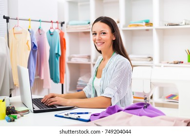 Beautiful seamstress using computer while working at her workshop.Dressmaker using laptop