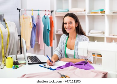 Beautiful seamstress working at her workshop.Dressmaker working