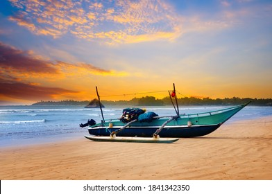 Beautiful seascape. Against the background of the sunset sky and the ocean, an old fishing boat. Sri Lanka