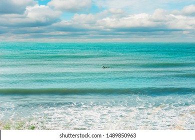 Beautiful seascape background. Calm turquoise sea water with swell waves, blue cloudy sky and lonely surfer paddling, early morning time.