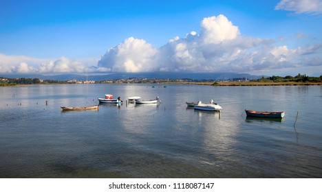 A beautiful seascape with boats and clouds in the sky, which are reflected in the water