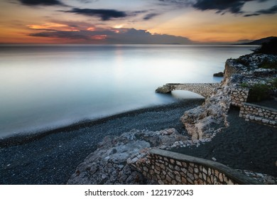 Beautiful seascape image taken with a long exposure of a scenic rock pier in the Caribbean with an amazing sunset on the horizon