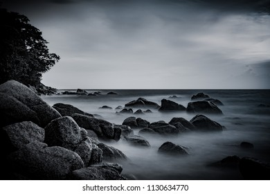 Beautiful seascape with motion of waves on the sea at Surin Beach, Phuket, Thailand. Tropical beach paradise holiday, dramatic beach background. Black and white taken.