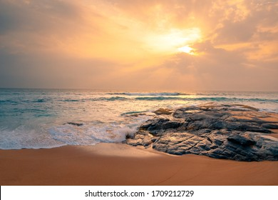 Beautiful seascape with ocean beach. Sandy beach with rocks and stones at the ocean coast under sunset sky with clouds on Sri Lanka island.