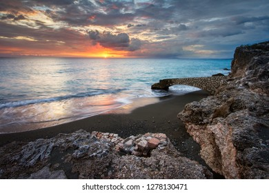 Beautiful seascape of an old stone pier overlooking the sunset