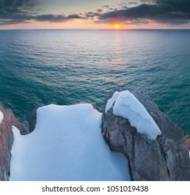 Beautiful seascape on the rocky coast in winter at sunset