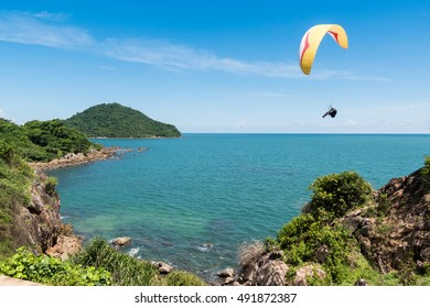Beautiful seascape with Paraglider flying in blue sky.