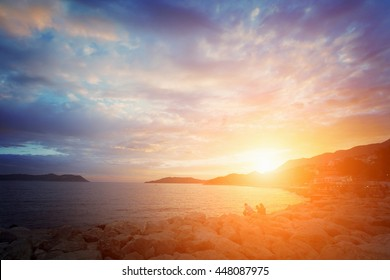 Beautiful seascape: people sit on the rocks by the sea at sunrise or sunset. Toned