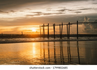 Beautiful seascape with remains of old wooden fishing bridge over sandy beach, famous photographed spot at Khao Pilai, Natai Beach, Phang Nga, Thailand.