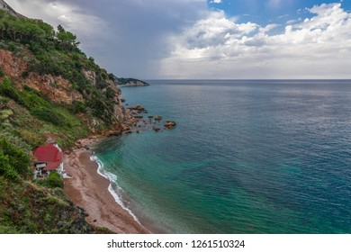 Beautiful seascape of the rocky coast and a small beach with a restaurant. Cloudy sky after rain and emerald waters of the sea of Elba island. Tuscany, Italy