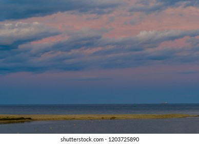 Beautiful seascape of sandbar jutting out into ocean under blue evening sky with light pink clouds and ship that is barely visible on horizon.