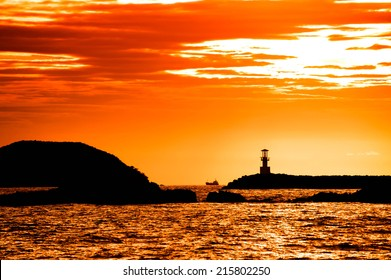 Beautiful seascape with silhouette lighthouse on sunset