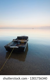Beautiful seascape with a single boat reflected in the still ocean at sunrise