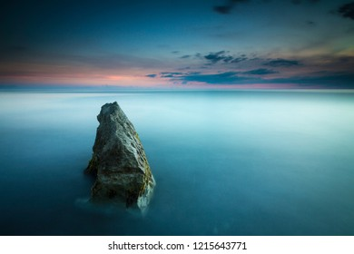 Beautiful seascape with a single rock leading out to the sunset