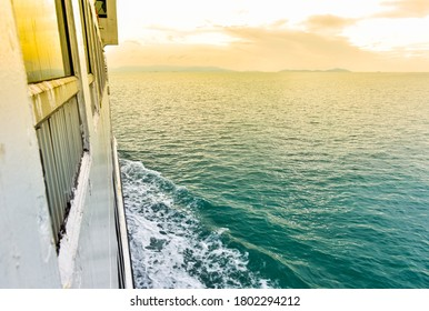 Beautiful seascape from starboard of ferry ship that were sailing to Samui Island. Sailing vessel on calm sea wave in cloudy day. Right side of ship and sea with orange blue gradient color in morning.