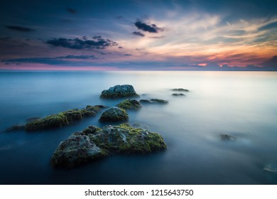 Beautiful seascape with stones leading out to the sunset taken with a long exposure