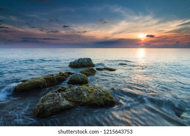 Beautiful seascape with stones leading out to the sunset