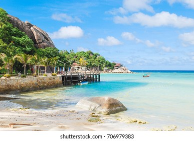 Beautiful seascape in summer season with rock on the beach, aqua and blue sea with boat floating on, big rock and coconut trees near small port, bungalow on coast side, white clouds and blue sky.