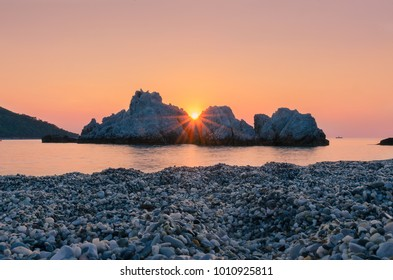 A beautiful seascape with sun between the rocks before down in Milia beach in Skopelos island!