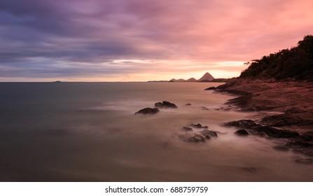 Beautiful seascape sunrise scenery with sea water flow and big rocks at Iriri beach Espirito Santo, Brazil. Long exposure shot.