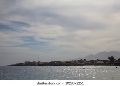 Beautiful seascape with a town in the background and thin clouds overhead